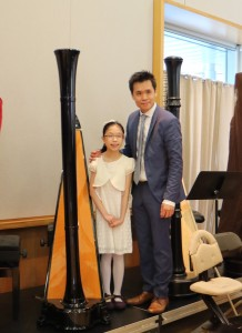 Chloe Yip poses with her teacher after performance of her two solos and with the Harp Orchestra at the Annual Concert 2016.